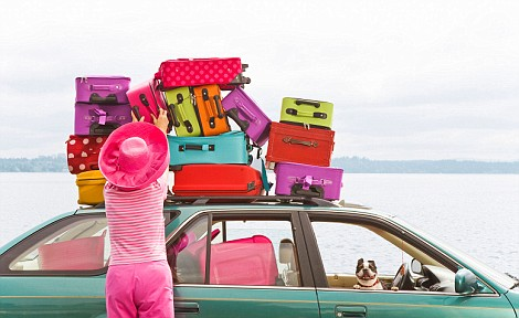 B3KM74 Woman adjusting stack of colorful suitcases on top of car. Image shot 2008. Exact date unknown.